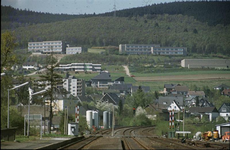 Das Schulzentrum. Am linken Bildrand erkennt man die Dreifachturnhalle. Das größere Gebäude im Vordergrund mit dem schwarzen Dach ist das katholische Gemeindezentrum.