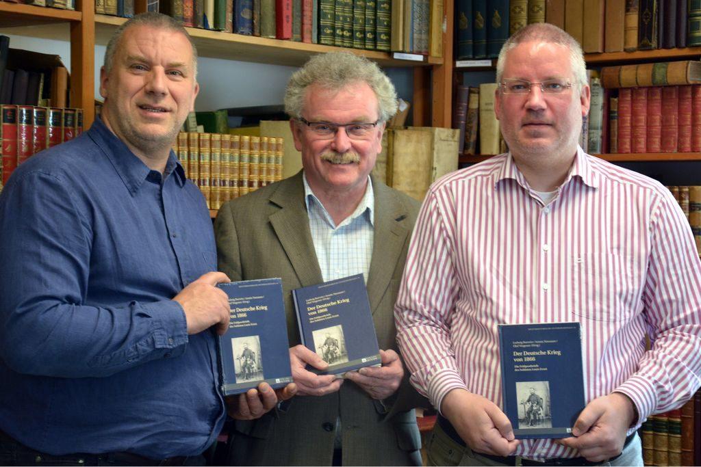 Buchvorstellung durch Armin Nassauer, den Siegener Stadtarchivar Ludwig Burwitz und den Historiker Olaf Wagener (von links nach rechts) in den Räumen des Antiquariates.